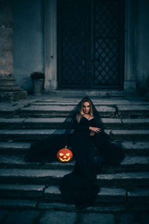 A young woman witch in black clothes sits near the old castle and holds in her hands a luminous pumpkin with a terrible face.