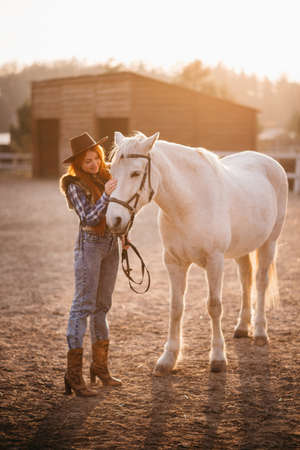 A young cowgirl woman stroking a horse in the sunset at her ranch.