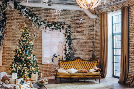 The loft-style room is decorated with New Years decorations. Luxurious vintage leather sofa and Christmas tree.