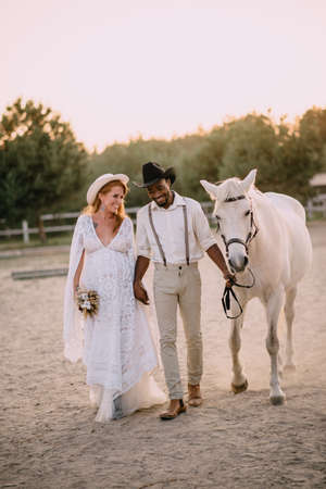 Interracial couple expecting a baby. A pregnant woman in a white dress and her cowboy husband go with a horse to the ranch. Wide shot. Stok Fotoğraf