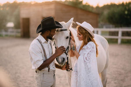 A young pregnant woman in a white dress and her cowboy husband are stroking a horse together at the ranch.