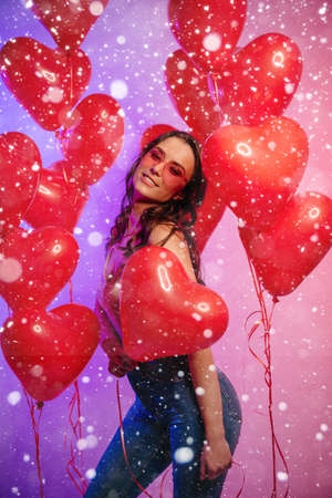 Valentines Day. Young joyful female dances among heart-shaped balloons.
