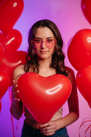 Valentines Day. Young attractive woman holding a heart-shaped balloon in her hands.