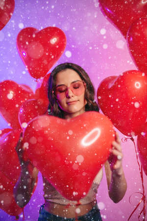 Valentines Day. Young attractive woman holding a heart-shaped balloon in her hands. Portrait with closed eyes.