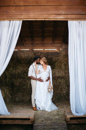 Interracial family. African man hugs his pregnant Caucasian wife tenderly. A rustic couple stands in a barn on a ranch on a summer afternoon.