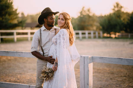 Interracial family. African man hugs his pregnant Caucasian wife tenderly. A rustic couple stand by a fence at a ranch at sunset. Stok Fotoğraf