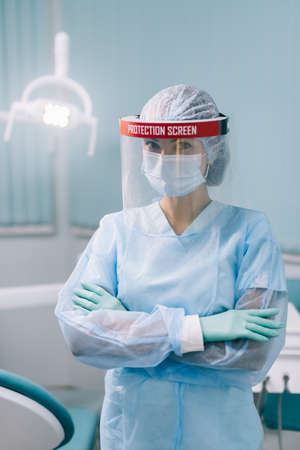 Portrait of a female dentist in a protective suit with a protective shield on her face in the dental office. Medium shot.