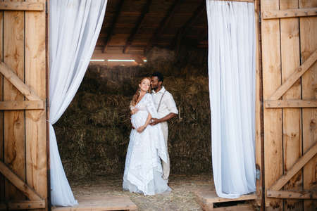 An interracial couple dressed in a rustic style is standing in a barn. African man hugs his pregnant Caucasian wife. Full-length portrait. Stok Fotoğraf