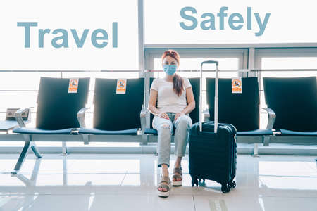 Safe travel. Young woman traveler in a medical mask is waiting for a flight at the airport terminal. Stickers on adjacent seats with the inscription - no sitting. Stok Fotoğraf