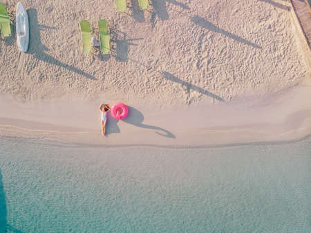 A young red-haired woman in a swimsuit lies on beach and enjoys a vacation. Top view. Stok Fotoğraf