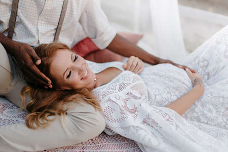 Interracial couple expecting a baby. A pregnant woman lies on the lap of her husband. Medium shot. Stok Fotoğraf