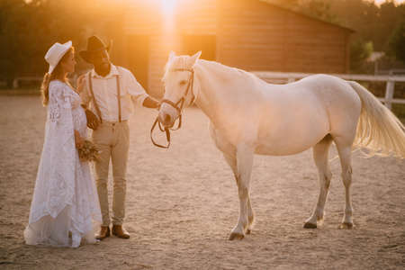 Interracial family. An African American man and his pregnant Caucasian wife stand near a horse on a ranch at sunset. Flare effect.