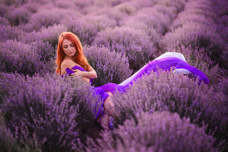 Romantic young red-haired woman sitting in lavender field at sunset. Medium shot.