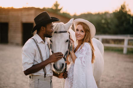 Interracial family. An African American man and his pregnant Caucasian wife stand near a horse on a ranch. Smiling woman looking at the camera.