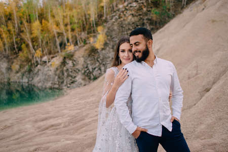 Newlyweds standing near beautiful lake. Middle Eastern groom and Caucasian bride embrace on the beach. Woman presses against her husbands back and looks at camera.