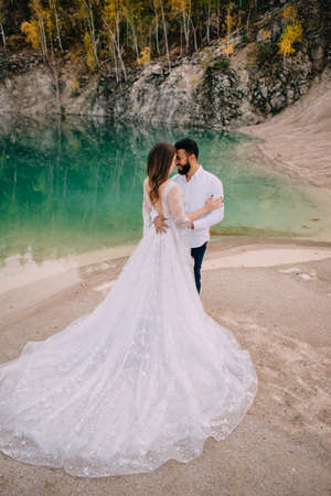 Newlyweds are standing near a beautiful lake. Middle Eastern groom and Caucasian bride embrace on the beach.