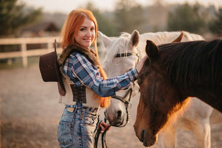 Cowgirl takes care of horses at ranch. Young red-haired woman affectionately stroking her horses and looking at camera. Stok Fotoğraf