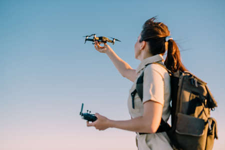 Quadcopter launch. Young woman tourist holds a drone in his hand lifting it up. Selective focus.