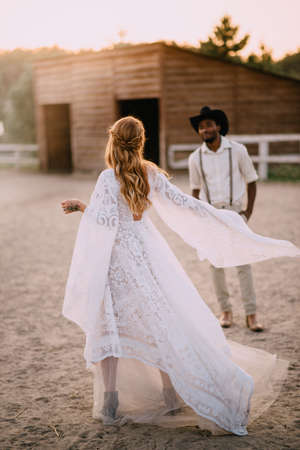 Cowboy style wedding. Caucasian bride in boho style dress dances in front of her African groom on ranch.