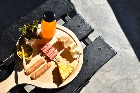 Food and drink concept, breakfast set with eggs, sausages, butter baked corn, toasts, orange juice and fresh vegetable on wooden table - Image