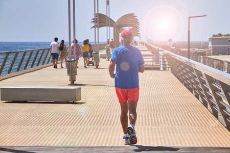 ALICANTE, SPAIN, CIRCA JUNE 2018, Active senior man jogging on the pier