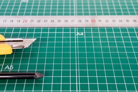 cutter, ruller and pencil on a green cutting mat