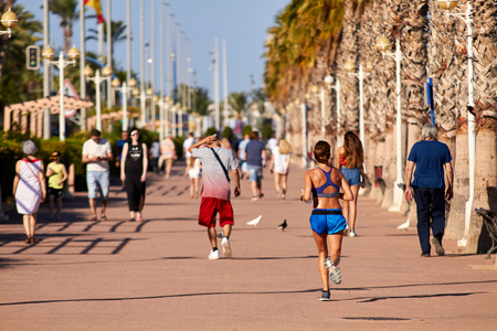 ALICANTE, SPAIN, CIRCA JUNE 2018 People walking and running on the promenade