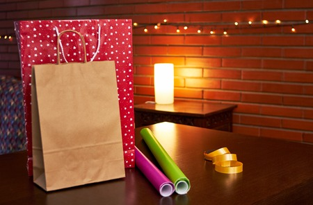 Shopping paper bags on a table with some gift paper wrap Imagens