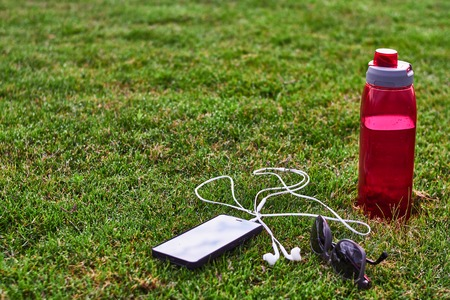 phone headphone water bottle and sunglasses on the grass