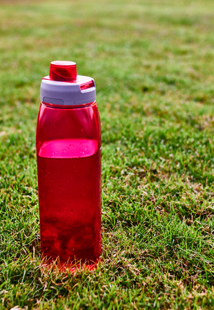 red water bootle on the grass
