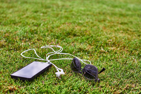 phone headphone and sunglasses on the grass