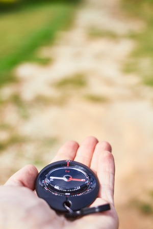 compass on a hand on a grass background
