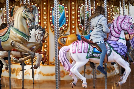 little girls back on a carousel 스톡 콘텐츠