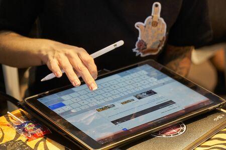 ALICANTE TATTOO FAIR CIRCA 2018 tattoo artist drawing a sketch on a tablet