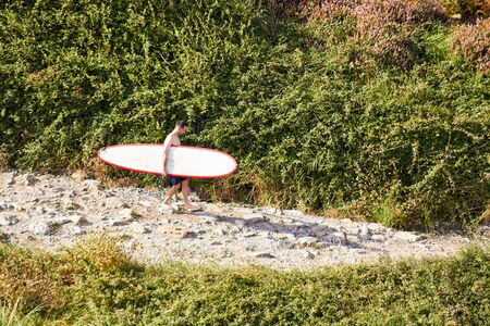 Young man with a surf board going to the beach
