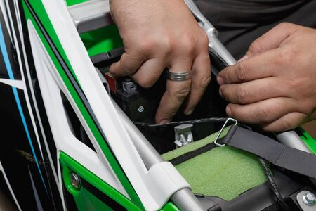 The wizard installs a new battery on the motorcycle after refueling and checking. Banco de Imagens