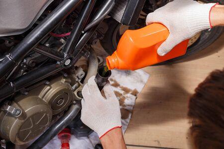 Het proces van het gieten van nieuwe olie in de motor van de motorfiets.