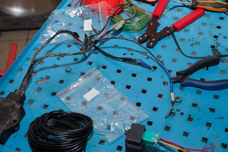 Master replaces electrical wires for sporty ignition of a motorcycle. Repair and maintenance of motorcycles