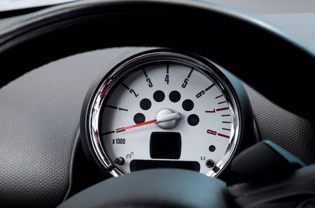 Car steering wheel and tachometer. Car dashboard. White automobile speedometer with numbers closeup.