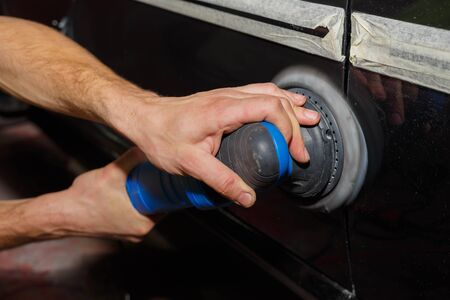 The master polishes the machine with a grinder with paste. Car care.