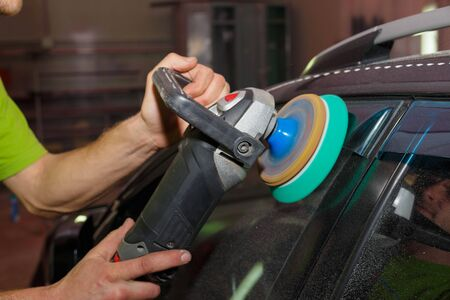 The master polishes plastic on a car with a grinder with paste. Car care.