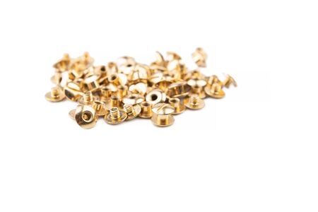 Close-up of a brass screw rivet, an accessory for working with electronics, construction, engineering, Golden metal isolated on a white background. Parts for furniture assembly. Furniture components