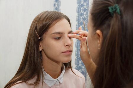 The process of removing excess tone cream. Makeup artist removes excess tone cream from model's face. Makeup artist aligns tonal crem on the face of the model. Applying tone to the skin.