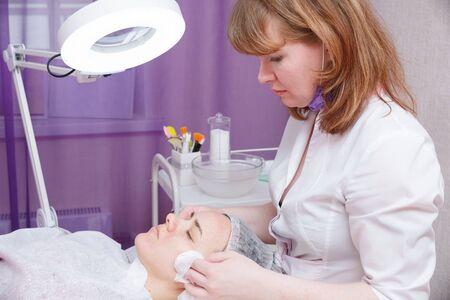 Kosmetikerin wäscht das Gesicht der Frau mit Wattepads. Vorbereitung für ein reinigendes Gesicht.