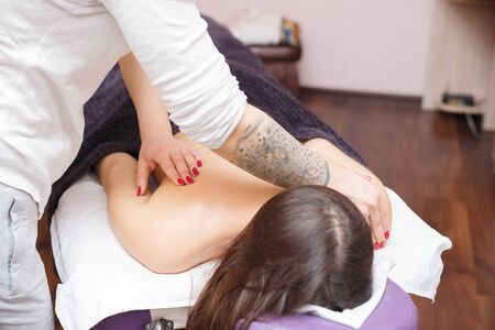 The master gives a back massage to the client. Providing massage services to a client in a private clinic. Фото со стока