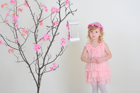 flew: Sad girl in a pink dress near a flowering tree with a bird that flew out of the cell.