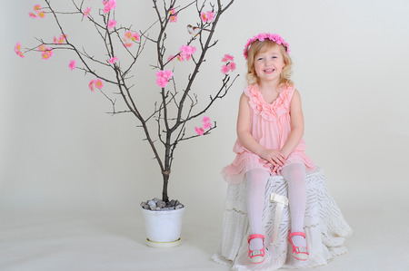 girl in a pink wreath and a pink dress with a bird on a flowering tree. laughs.