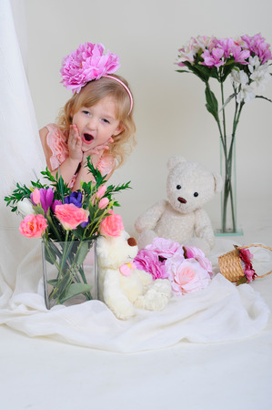Surprised girl in a pink dress near the bouquets of flowers sitting on the floor photo