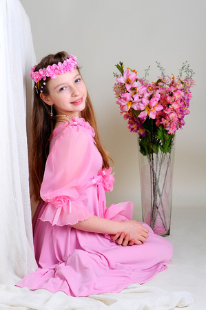 girl in a pink dress sits near a vase of flowers photo