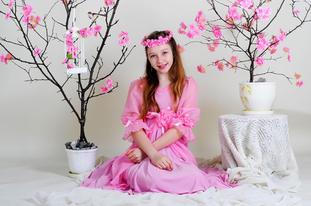 girl in a pink dress sitting near blossoming tree with bird and empty cell photo